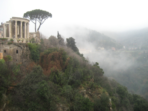 A magical Roman Temple in Tivoli over looks the valley in the fog.