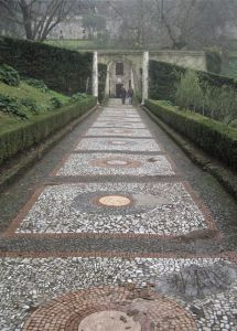 A stone mosaic walkway leads to a special doorway in an Italian Renaissance garden.